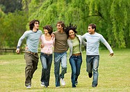 Group of young friends with arms around each other, skipping across field