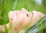 Young woman lying in grass, close-up of face