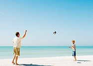 Father and son throwing ball on beach