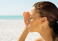 Woman shading eyes on beach, close-up