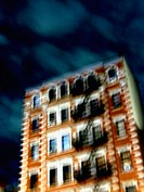 A New York apartment building is captured at night with a blury, pastel effect