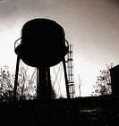 The sillouette of a water tower is captured in black and white against a dramatic sky