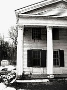 An old weathered colonial home in New England is captured diring the winter. Forlorn and abandoned feeling