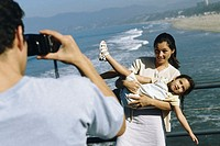 Father taking a photograph of his wife and daughter