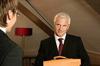 Mature businessman with a briefcase is standing in front of a young businessman