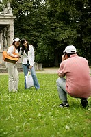 Man taking a picture of two Asian women in a park