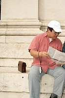Asian man sitting on stairs while looking at a map