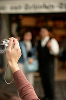 Woman taking a picture of two people in front of a shop, selective focus