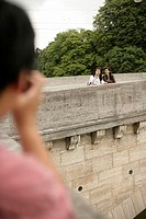 Man taking a picture of two Asian women on a stone-bridge, selective focus