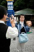 Asian man taking a picture of an Asian woman who is holding up two fingers, selective focus
