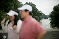 Asian heterosexual couple is standing on a bridge in front of a river amongst trees, focus on background