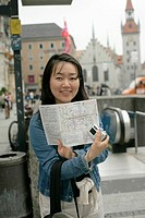 Asian woman on a plaza holding up a map of interurban train, selective focus