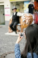 Woman taking a picture of a man with a hat who is leaning against the figure of a lion, selective focus
