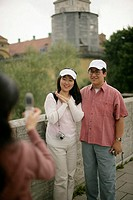 Person is taking a picture of an Asian couple, selective focus