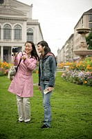 Young Asian woman with a camera standing next to a younger woman in front of a park and is laughing, selective focus
