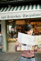 Young Asian woman with a map is standing in front of a shop, selective focus