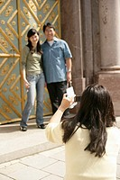Female taking a picture of an Asian man and a woman who are standing in front of an ornate door, selective focus