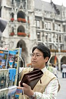 Asian man looking for a map in a rack, selective focus