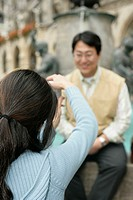 Woman with black hair taking a picture of an Asian man who is sitting on the brim of a fountain, selective focus