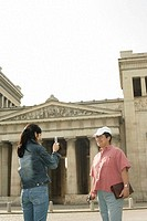 Woman is taking a picture of an Asian man in front of an antique building
