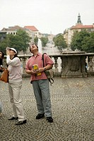 Three Asian people with cameras looking up, focus on foreground
