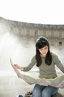 Young Asian woman with a map sitting in front of a fountain