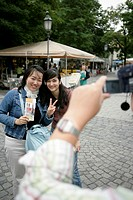 Man filming two Asian women, selective focus