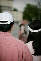Heterosexual Asian couple from behind wearing white caps, selective focus