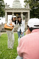 Man taking a picture of two Asian women in front of a monument, selective focus