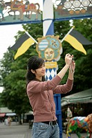Young Asian woman standing in front of a maypole and is taking pictures with a camera, selective focus