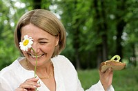 Mature woman smiling with a sandwich and a flower in her hand