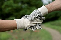 Couple wearing garden gloves, shaking hands