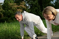 Mature couple having a footrace, starting block position