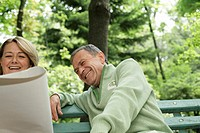 Mature couple sitting on a bench, laughing
