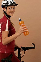 Woman with a mountain bike holding a bottle in her hand and looking at camera