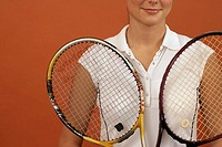 A female tennis player holding two rackets