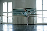 A female ballet dancer exercising a attitude at ballet bare