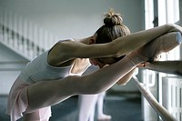 Female ballet dancer doing stretching exercising at a ballet bare