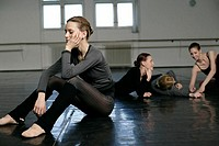 A female ballet dancer sitting being the odd one out of a group