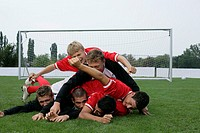 Soccer players lying in a crowd on grass (thumbnail)