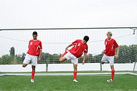 Soccer players doing stretching exercise in front of the goal