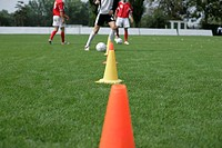 Soccer player running slalom with a football around marks