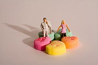 A man and woman figure surrounded by candy hearts look for love