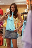 Young woman holding a top in a clothing store (thumbnail)