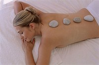 High angle view of a young woman with therapeutic stones on her back
