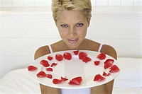 Young woman holding a plate with rose petals