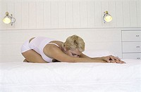 Young woman stretching on the bed