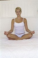 Portrait of a young woman sitting in a lotus position