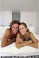 Portrait of a young couple lying on a bed (thumbnail)