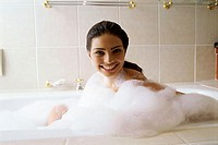 Portrait of a young woman taking a bubble bath
